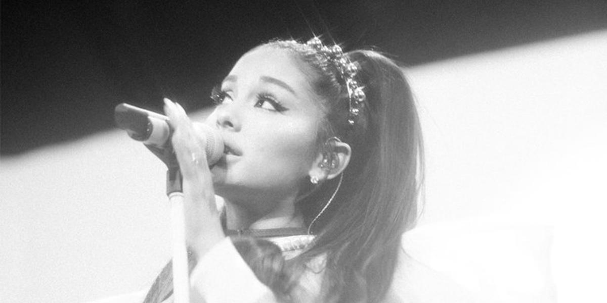 Cantora Ariana Grande segurando um microfone que está no pedestal