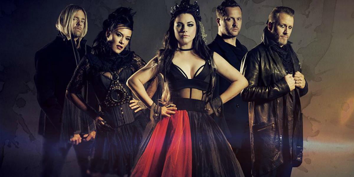 Banda Evanescence com trajes pretos. Amy Lee está com um vestido preto e vermelho