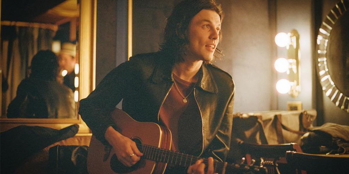 Cantor James Bay sentado em uma sala de espelhos com um violão
