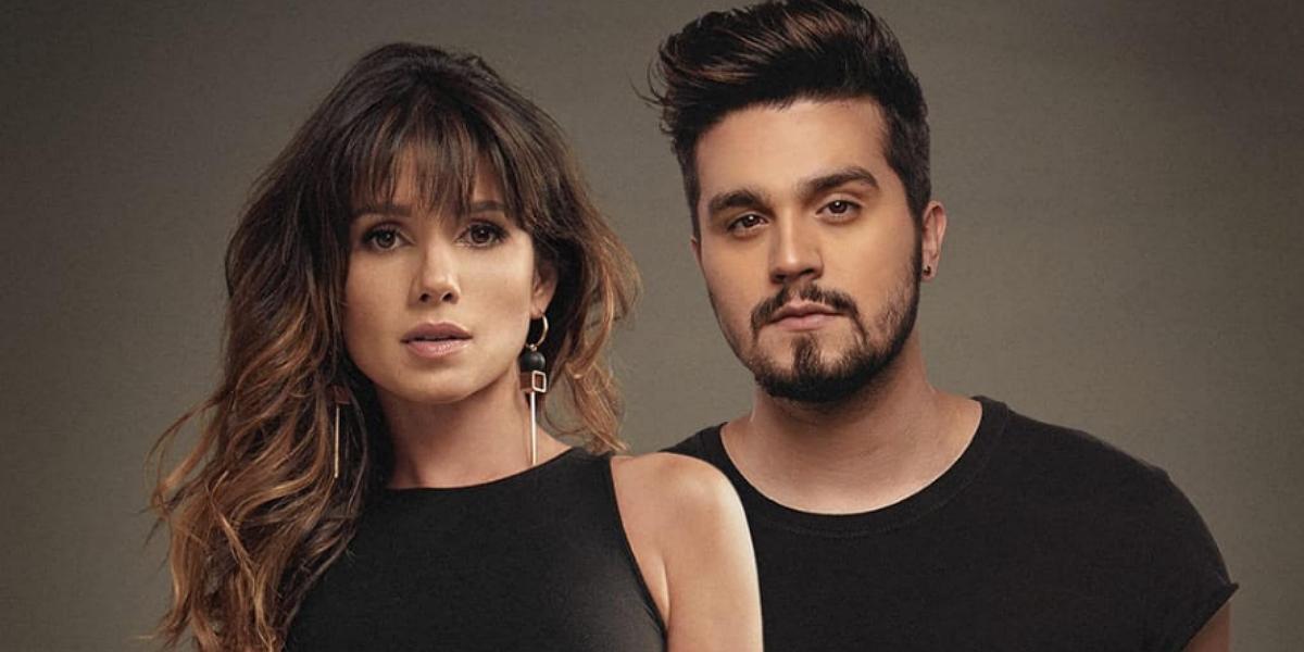 Paula Fernandes e Luan Santana usando roupas pretas em um fundo marrom
