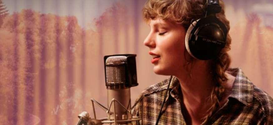 taylor swift em frente a um microfone em estudio cantando no especial do album folklore no disney plus