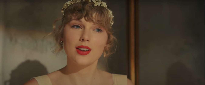 taylor swift no videoclipe de willow primeiro single do album evermore ela olha para a frente vestindo tiara e batom vermelho