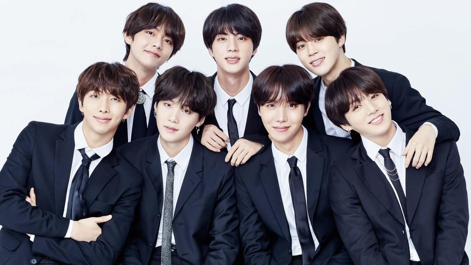 """A foto apresenta todos os integrantes do BTS, grupo sul-coreano de k-pop, vestidos com paletó e gravata. Há três membros do grupo em pé e quatro à frente. A foto ilustra a matéria BTS: entenda caso de racismo que o grupo sofreu por radialista alemão"""""""