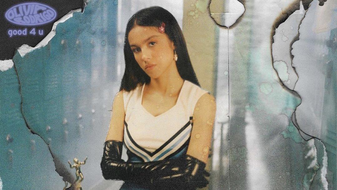 """A imagem mostra um recorte da capa do single """"good 4 u"""" da cantora Olivia Rodrigo. Ela está usando luvas pretas com os braços cruzados, usando uma roupa de líder de torcida e olhando para frente séria."""